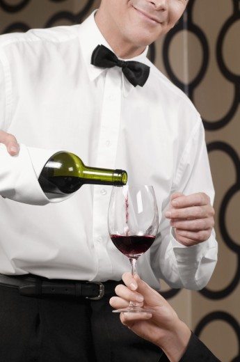 Waiter pouring red wine into a wine glass held by a woman : Stock Photo
