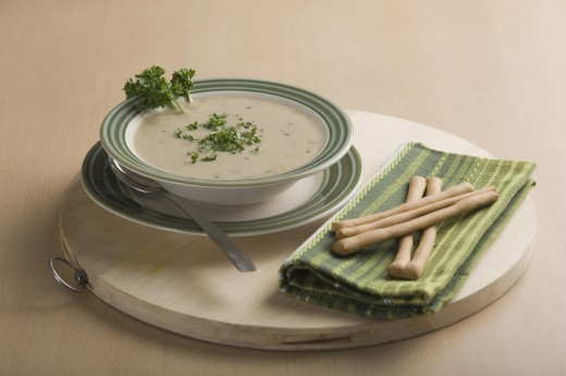 Close-up of a bowl of soup served with breadsticks : Stock Photo