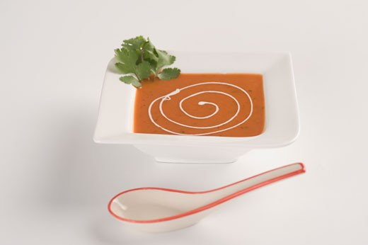 Close-up of a bowl of tomato soup garnish with cream : Stock Photo