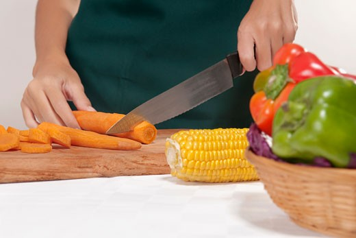 Mid section view of a woman cutting vegetables : Stock Photo
