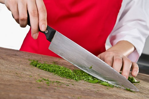 Mid section view of a female chef chopping cilantro leaves with a knife : Stock Photo