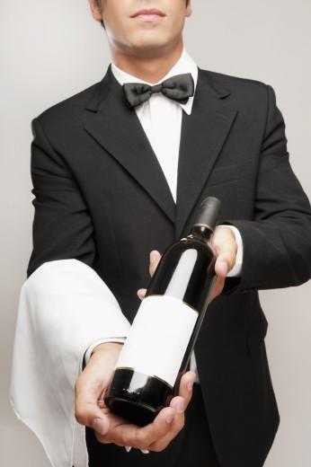Waiter holding a bottle of wine : Stock Photo