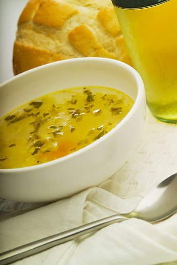Close-up of a bowl of soup with a loaf of bread : Stock Photo