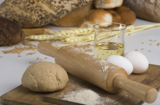 Eggs and dough with rolling pin on cutting board : Stock Photo