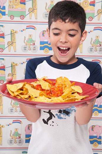 Close-up of a boy holding a platter of nachos : Stock Photo