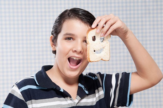 Boy holding a slice of bread : Stock Photo