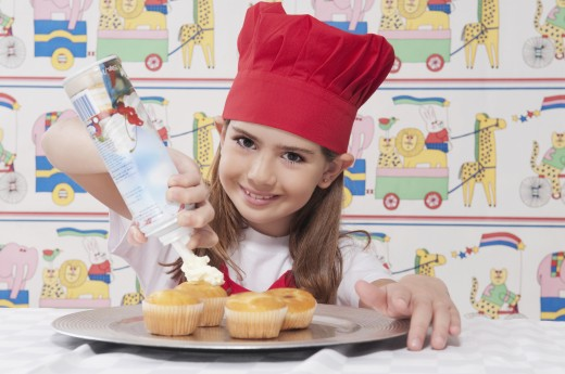 Portrait of a girl putting whipped cream on cupcakes : Stock Photo