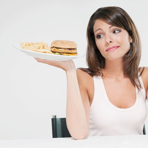 Woman holding a hamburger in one hand and frowning : Stock Photo