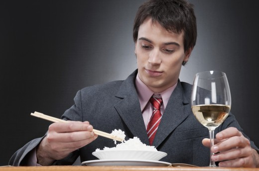 Close-up of a businessman eating rice with chopsticks : Stock Photo