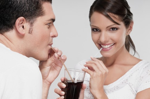 Couple sharing a cola beverage : Stock Photo