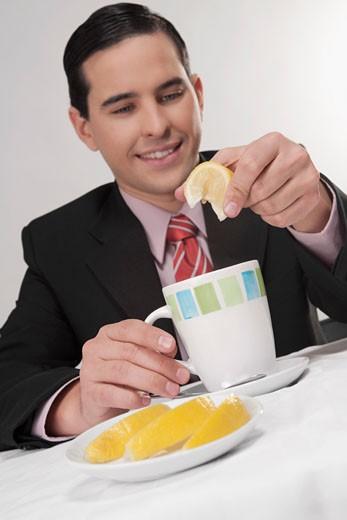 Businessman squeezing lemon into tea : Stock Photo