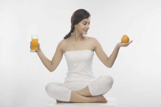 Stock Photo: 1884-62898 Woman holding an orange and a glass of orange juice