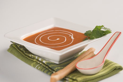 Close-up of a bowl of tomato soup served with breadsticks : Stock Photo