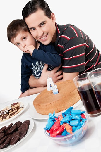 Portrait of a man and his son with a birthday cake in front of them : Stock Photo