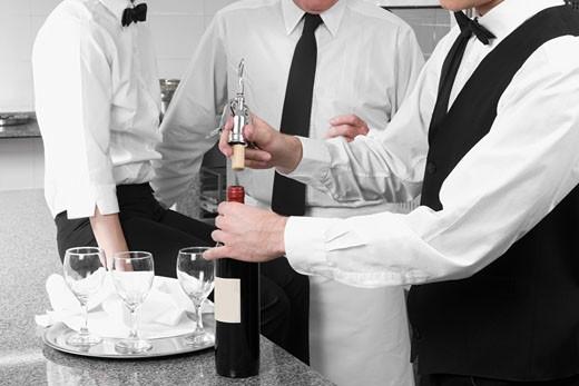 Waiter opening a wine bottle : Stock Photo