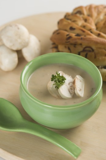 Bowl of soup served with mushroom and a loaf of bread : Stock Photo