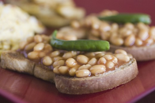 Close-up of baked beans on toasts with green chillies : Stock Photo