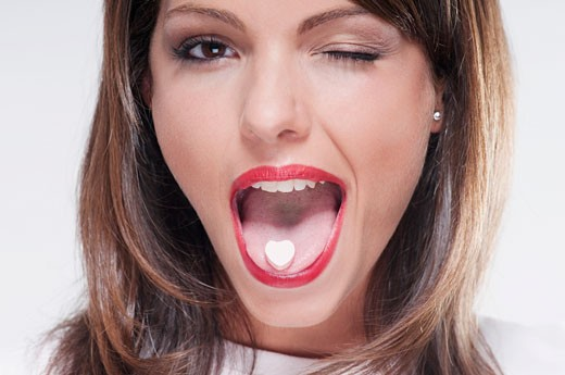 Woman winking with mint candy on her tongue : Stock Photo