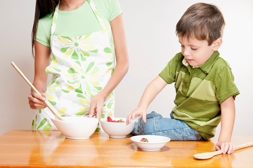 Boy helping his mother in cooking : Stock Photo