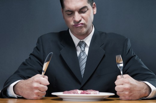 Businessman frowning at a raw steak : Stock Photo