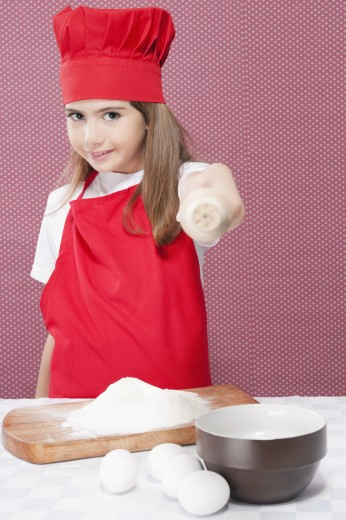 Stock Photo: 1884-63798 Portrait of a girl showing a rolling pin