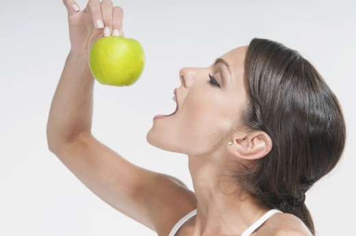 Woman eating a green apple : Stock Photo