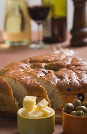 Close-up of a loaf of bread with cups of butter and olives : Stock Photo