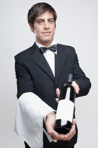 Portrait of a waiter holding a bottle of wine : Stock Photo