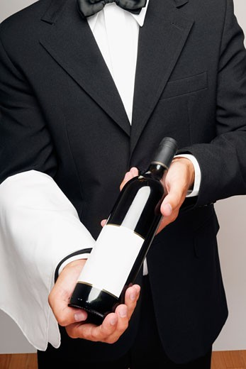 Mid section view of a waiter holding a bottle of wine : Stock Photo