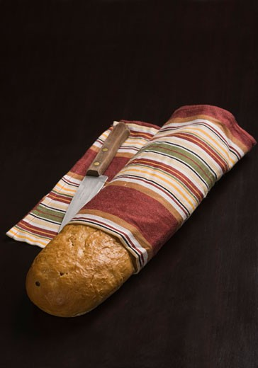 Close-up of a loaf of bread with a knife : Stock Photo