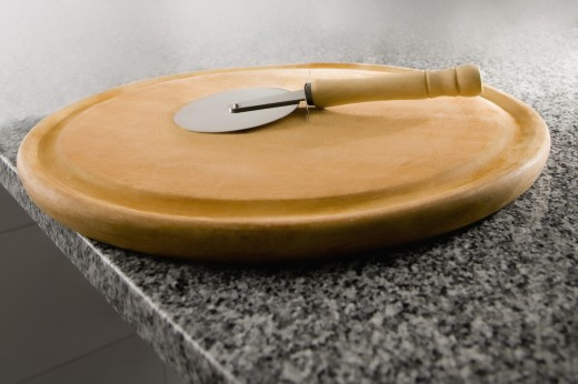 Stock Photo: 1884-64610 Pizza cutter on a cutting board