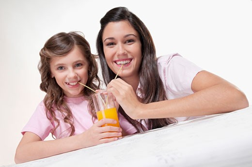 Woman with her daughter drinking juice : Stock Photo