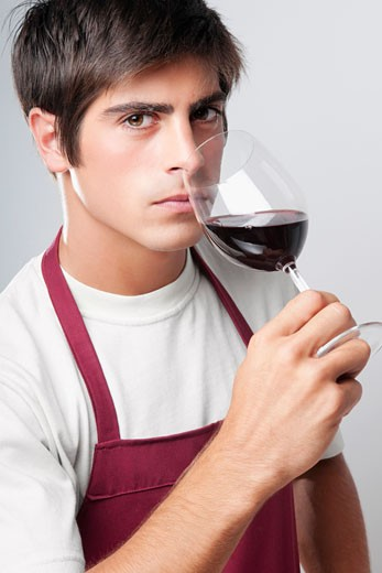 Close-up of a man smelling a glass of red wine : Stock Photo