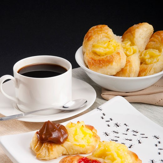 Stock Photo: 1884-64932 Close-up of danish pastries served with a cup of black coffee