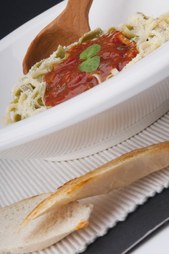 Stock Photo: 1884-65239 Close-up of a ladle in fettuccine topped with tomato sauce