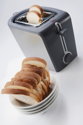 Stock Photo: 1884-65735 Close-up of white breads in a bowl with a toaster