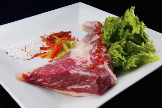 Stock Photo: 1884-65843 Close-up of a steak with ground red chilies and peppers