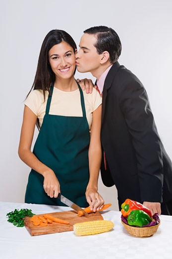 Man kissing his wife cutting vegetables : Stock Photo