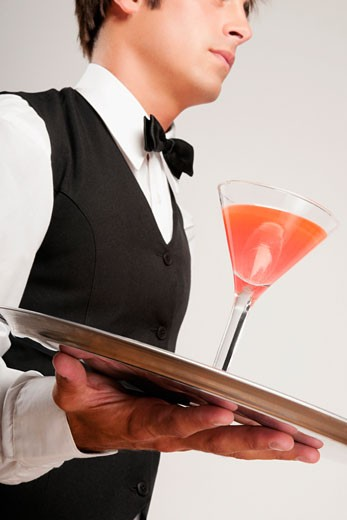 Close-up of a waiter holding a cocktail on a tray : Stock Photo