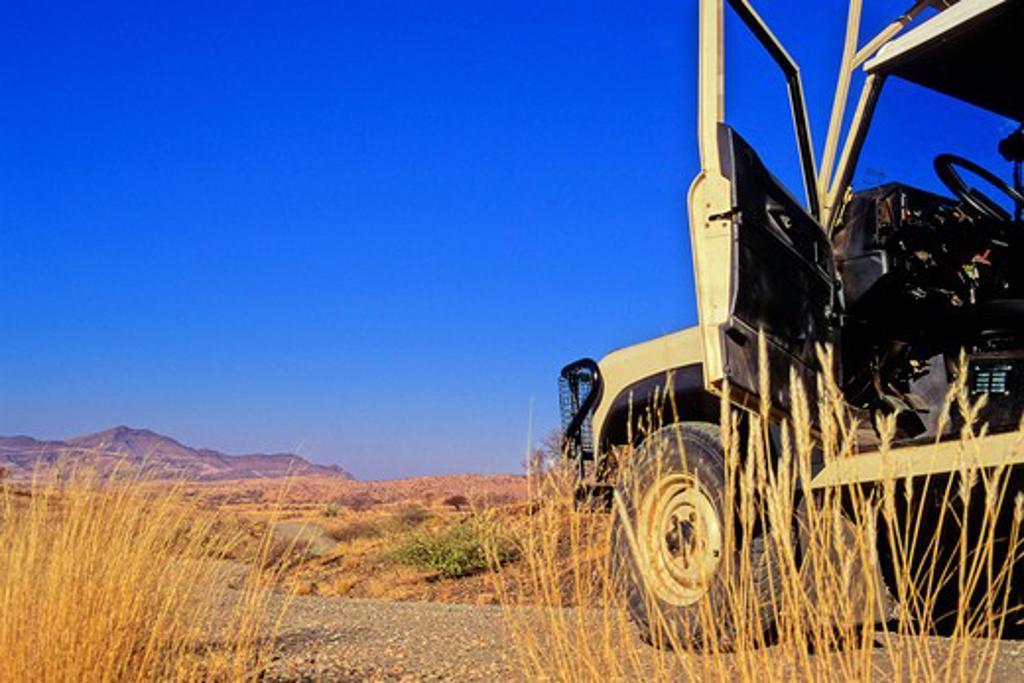 Namibia, Open door of Land Rover on savanna grassland road : Stock Photo