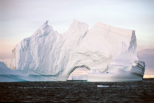 Antarctica, Antarctic Peninsula, Iceberg showing wind shaped arch and ocean water and sky : Stock Photo