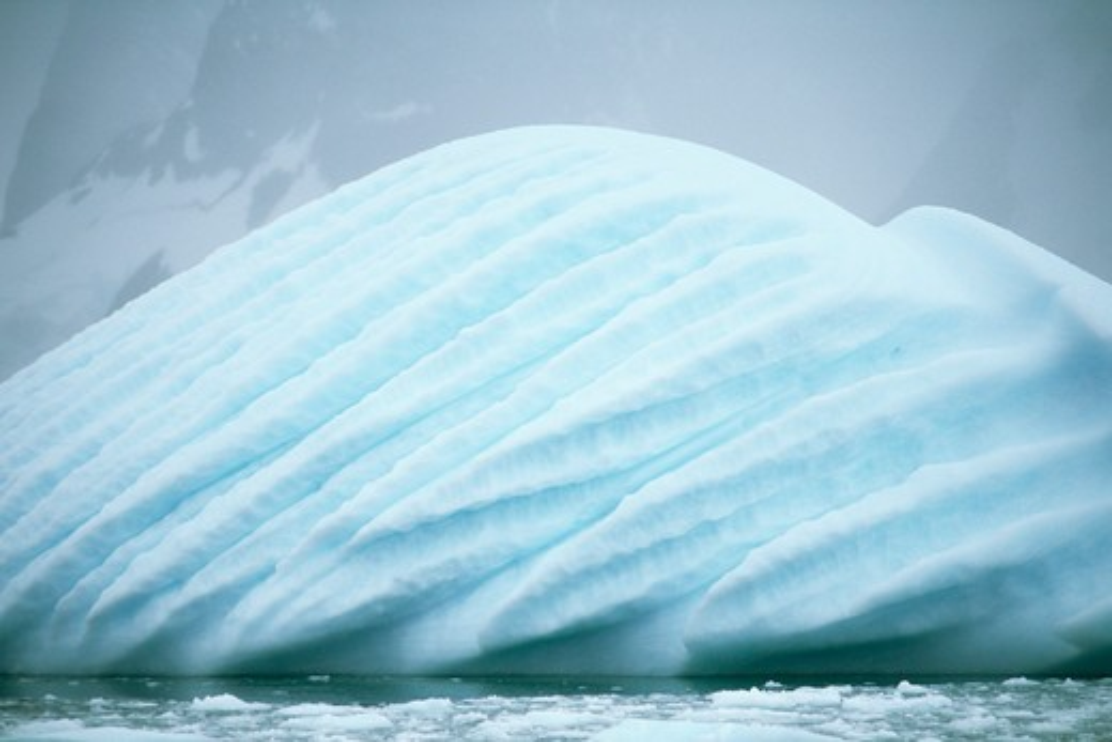 Antarctica, Antarctic Peninsula, Ice fog and cloud hangs over strange blue iceberg - revealing wind shaped surface : Stock Photo