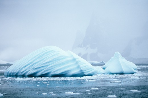 Stock Photo: 1885-22408 Antarctica, Antarctic Peninsula, Ice fog and cloud hangs over strange blue iceberg - revealing wind shaped surfaces of two icebergs