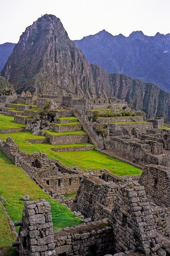 Stock Photo: 1885-22495 Peru, Inca ruins at Maccu Piccu - showing central courtyard and Huayna Piccu landmark, grass terraces, ancient stonework - dark clouds and mountain peaks in background, tourist in view