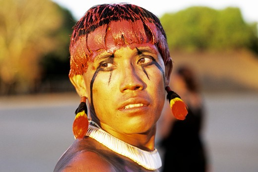 Stock Photo: 1885-22516 Brazil, Xingu Amazon tribesmen  with face decorated in jempapo and red-yellow paint made form urucum seeds and hear color form rurucum mixed with water and mud, face in traditional black patterns dyed with jemipapo plant, necklace from traditional white shell beads