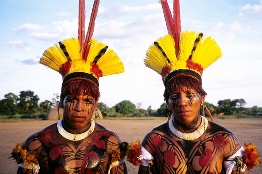 Brazil, Xingu Amazon tribesmen  with face decorated in body paint including urucum and yellow tucan feathers and natural dyes in traditional patterns : Stock Photo