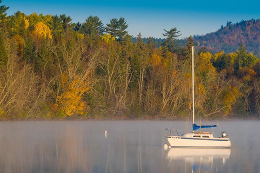 USA, New Hampshire, Lake Umbagog, Lake Umbagog with yacht in autumn : Stock Photo