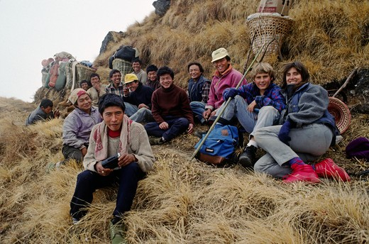 TREKKERS with a smiling group of PORTERS AND SHERPAS on a HIMALAYAN PASS - BODHA HIMAL, NEPAL : Stock Photo