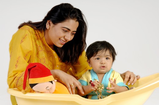 Indian Baby playing in yellow bath tub with mother ; MR : Stock Photo