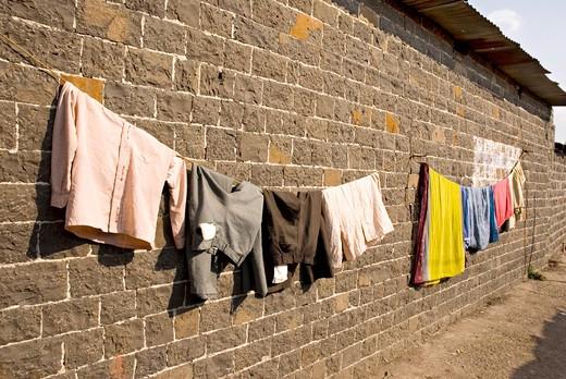 Stock Photo: 1886-47947 Black stone wall and hanging cloths drying on thin rope in village Salunkwadi ; Tal. Ambajogai ; Dist. Beed ; Maharashtra ; India